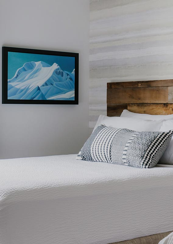 A hotel bed nicely made with an art print of a glacier hanging on the wall next to it.