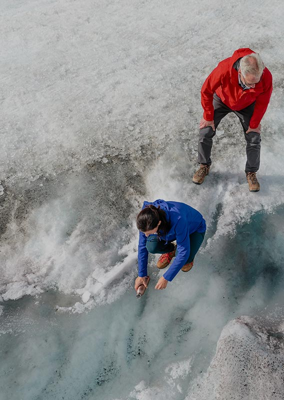 Couple on Athabasca glacier collecting water from glacial stream