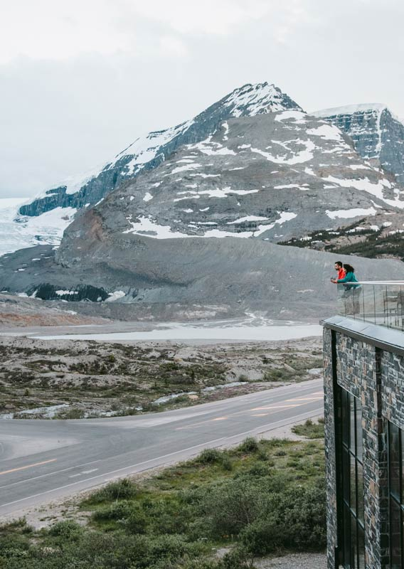 Two people stand on a viewing balcony, looking towards the Athabasca Glacier