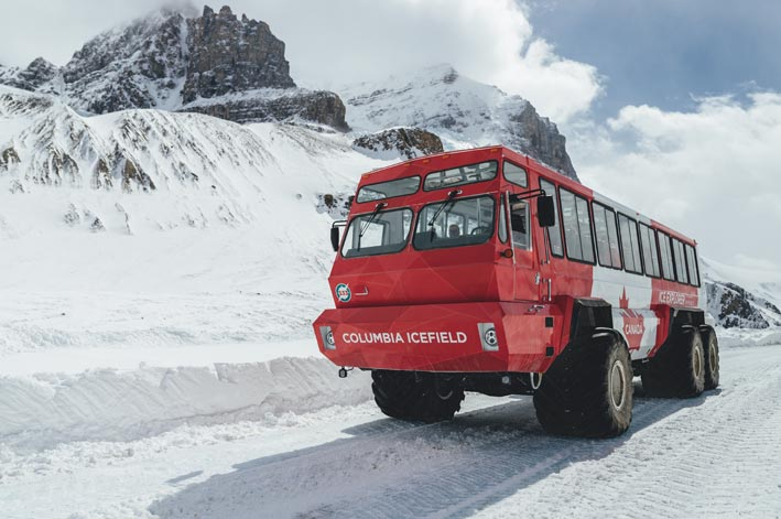 A red and white Ice Explorer vehicle moves on an ice road below a rocky mountainside