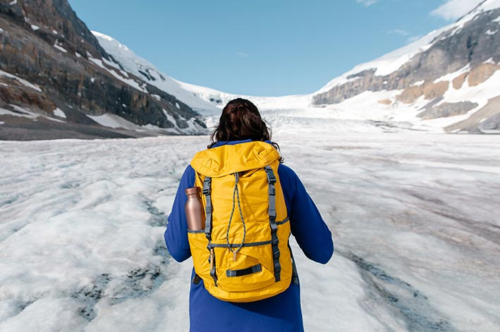 A person in a blue jacket and yellow backpack looks out across a vast glacier.