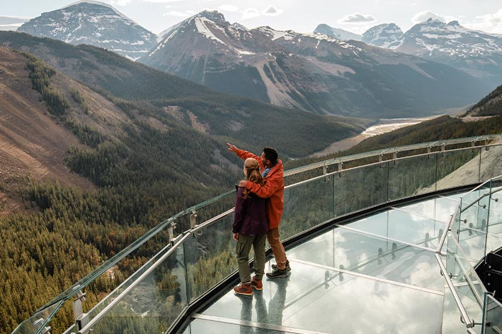 Two people stand on a glass walkway high above a forested valley.
