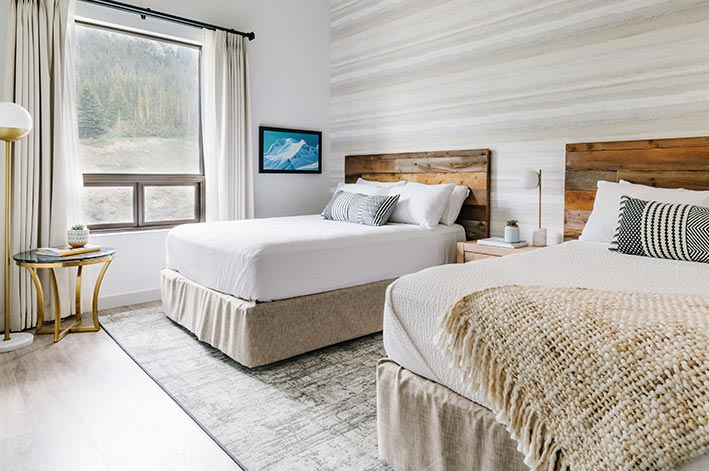 Glacier View Lodge room with two queen beds and views of a forested mountainside
