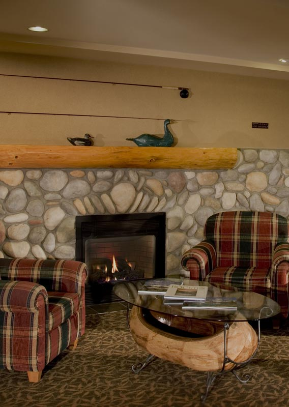 The lounge in Lobstick Lodge with chairs and fireplace