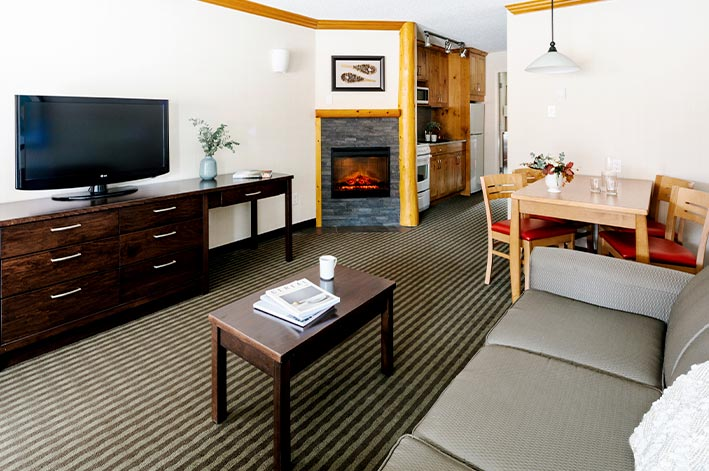 A living area in a hotel room with coffee table and fireplace.