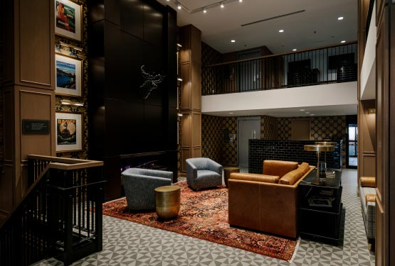 A tall lobby with leather lounge chairs and couches.