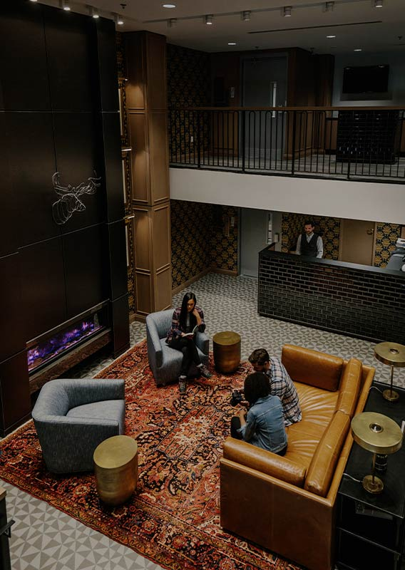 A hotel lobby with people sitting on couches and chairs.