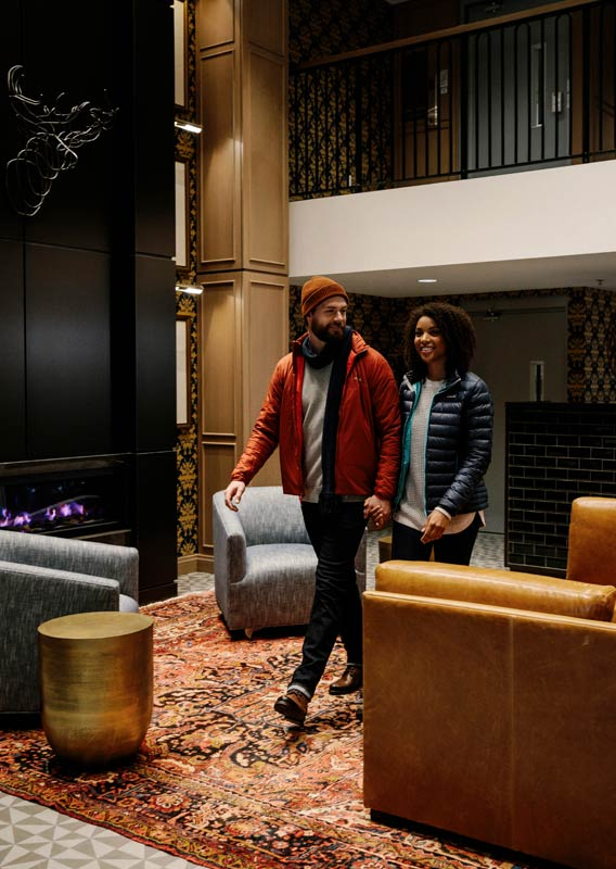 Two people walk through an elegant lobby, dressed for the outdoors.