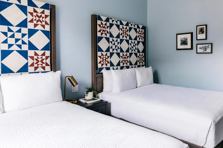 Two beds with red and blue quilted headboards, with artwork on the wall alongside.