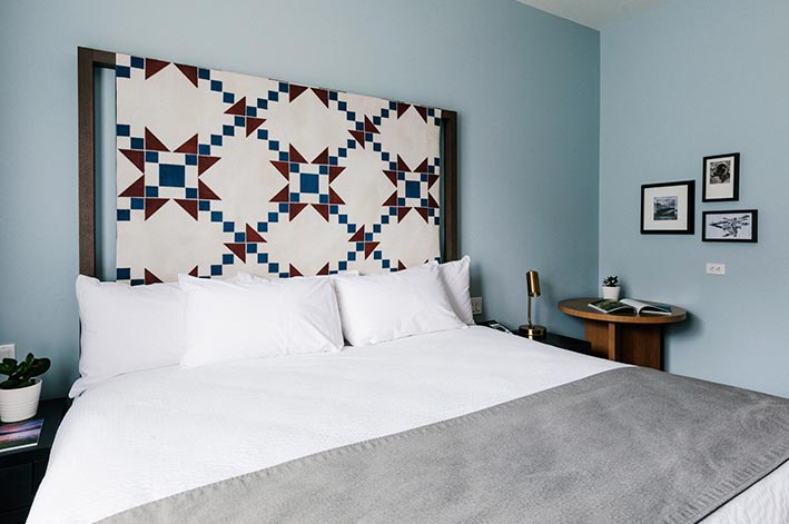 A king bed in a hotel room with a quilted headboard.