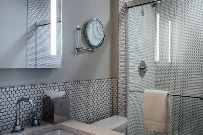 Sink, toilet mirrors and shower in a bathroom.