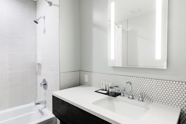 A sink and shower with white tiles and countertops.