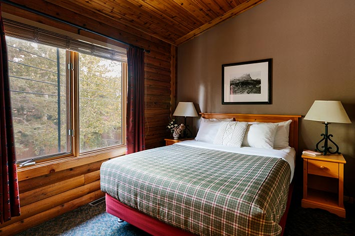 A bed in a wooden cabin next to a large window looking out to trees