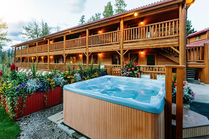 A hot tub outside of a two-story lodge building.