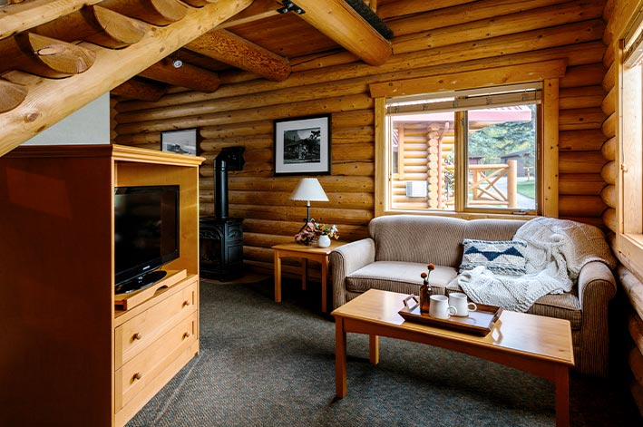 A living area in a wooden cabin, with sofa and coffee table.