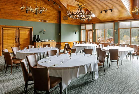 A rustic meeting room set up with four round tables.