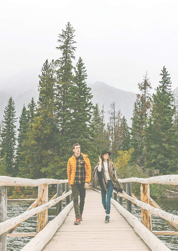 Two people walk across a wooden bridge from a small treed island.