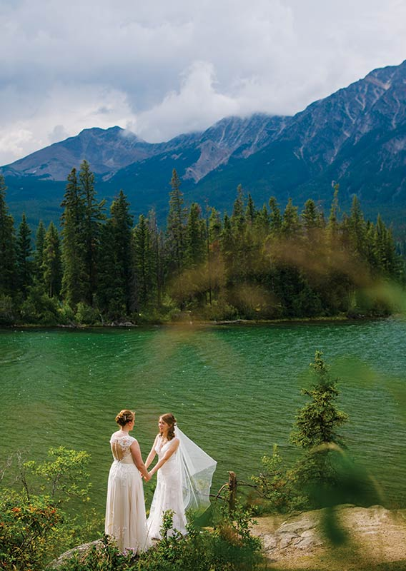 Two brides face each other holding hands at the shore of Pyramid Lake