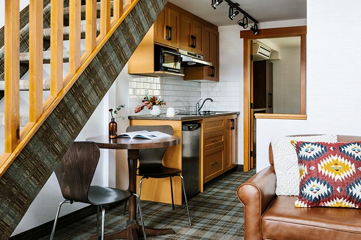 A hotel room kitchen below a wooden staircase.