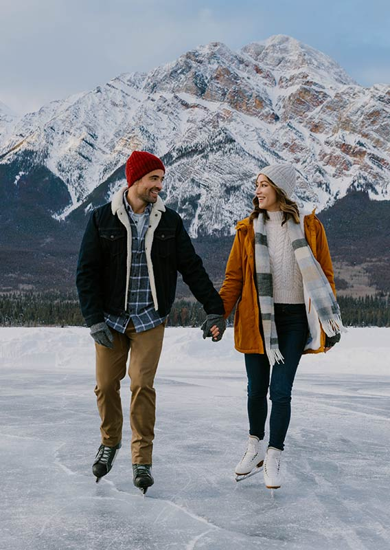 Two people hold hands while skating on a frozen lake.
