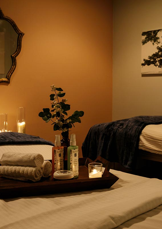 Two spa beds in a dimly-lit room with candles around.