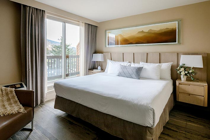A hotel room bedroom with a king bed and sliding door balcony