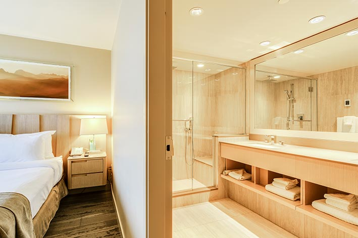 A hotel room with adjacent large bathroom