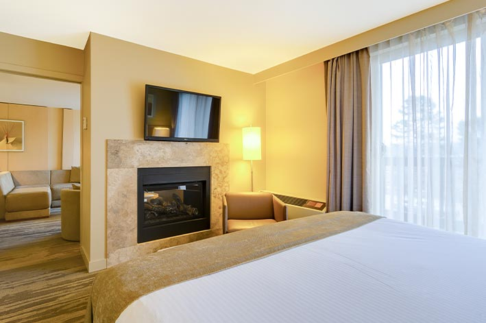 A hotel room bed facing a fireplace and television
