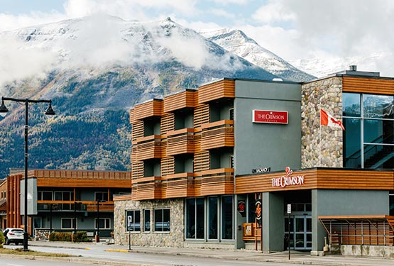 The Crimson hotel along a road against a backdrop of snow-dusted mountains.