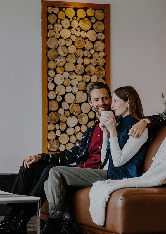 Two people sit in a leather sofa in a rustic-modern hotel lobby
