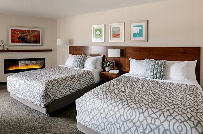 Two beds in a hotel room with a fireplace beside them