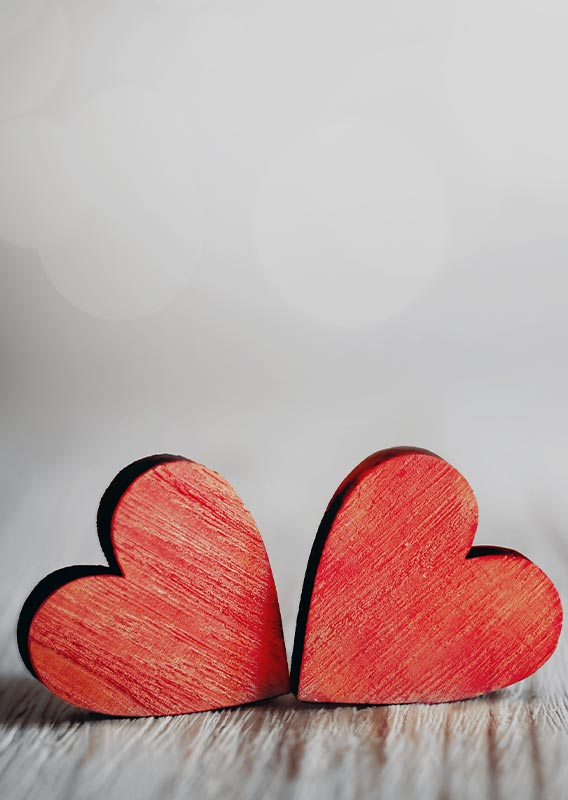 Two red wooden hearts arranged on a beige backdrop.
