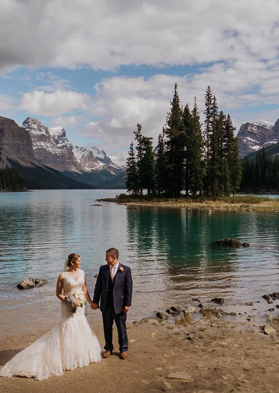 A bride and groom pose on a frozen Pyramid Lake at the base of a snowy mountain