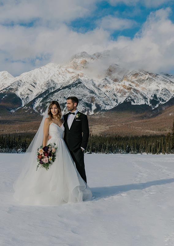 A newly wed couple stands on a snowy frozen lake.