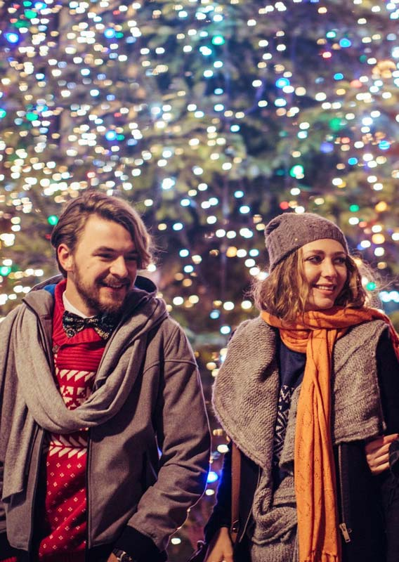 A group of people dressed for the winter smile in a Christmas-decorated place.