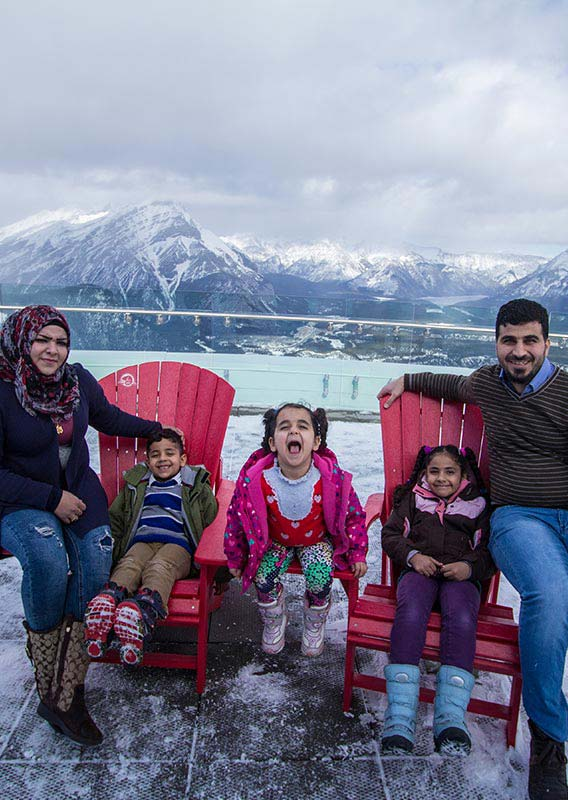 Family sit on the observation deck at the Banff Gondola summit.