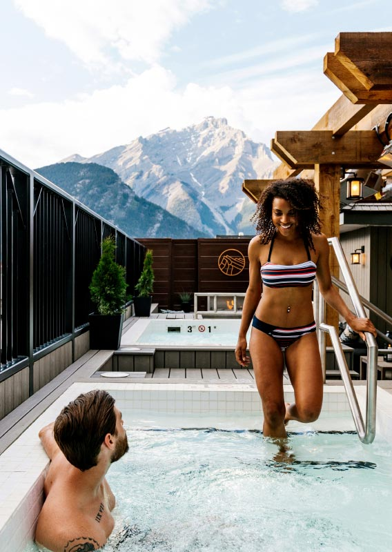 Two people relax in a rooftop hot tub with views of mountains in the distance.