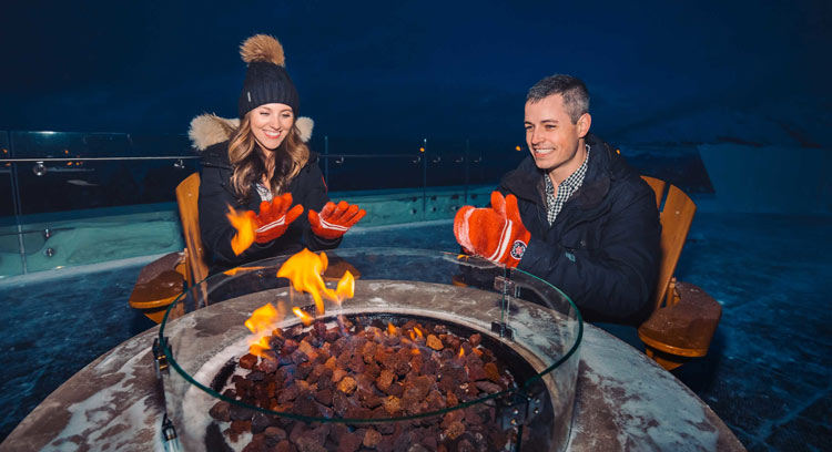 Guests warming up by the firepit at the top of Sulphur Mountain