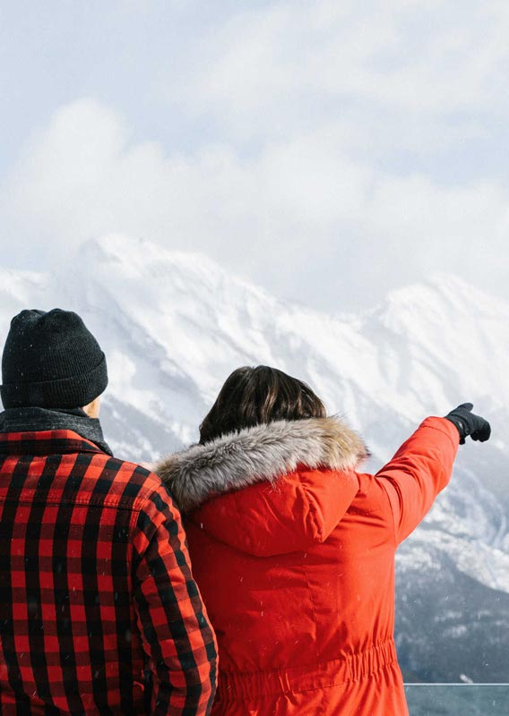 Couple looking at the mountains from the top of Sulphur Mountain in winter