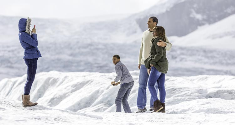 A family poses for a photo on an icefield