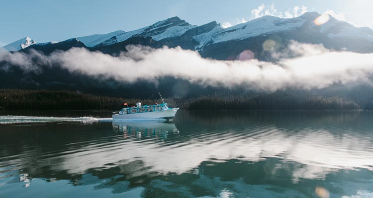 A boat glides along a mountain lake under light mist