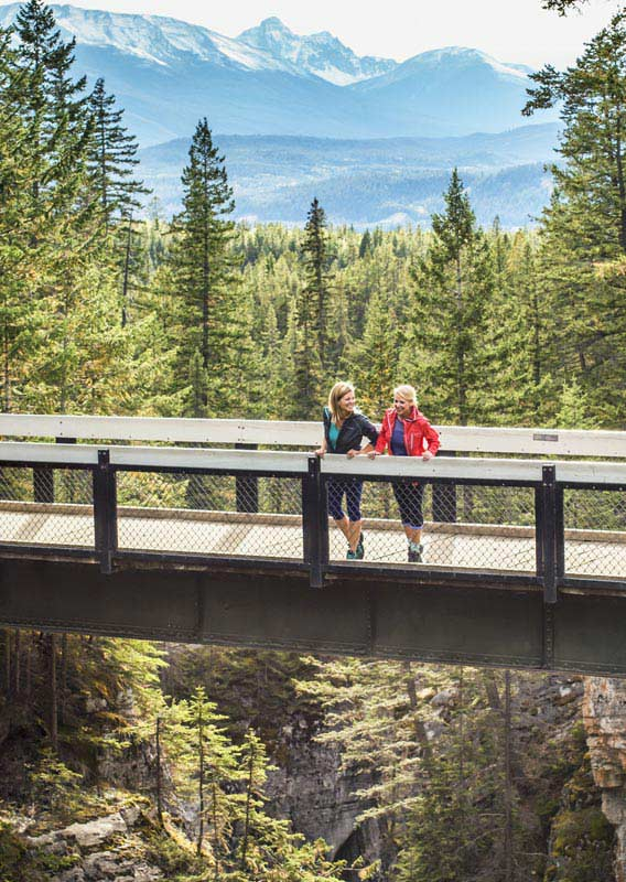 Two women stand on a bridge overlooking a rocky canyon