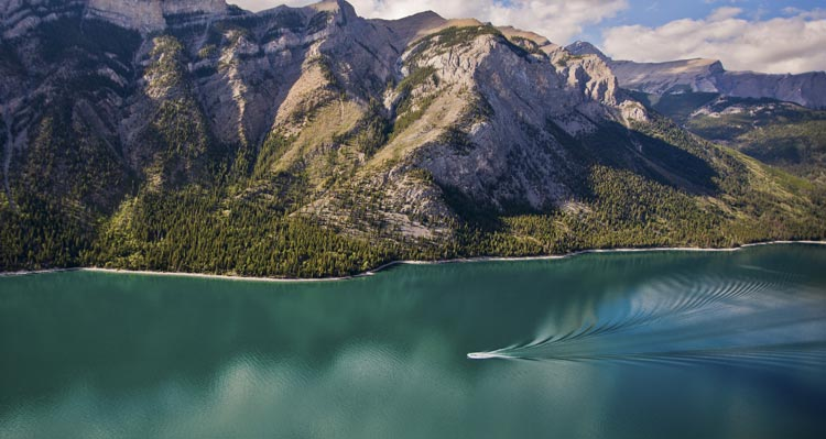 An aerial view of a boat cruising along a large blue-green lake below tree-covered mountains.