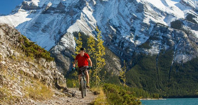 A cyclist rides on a narrow dirt trail above a blue lake with snow-covered mountains behind.