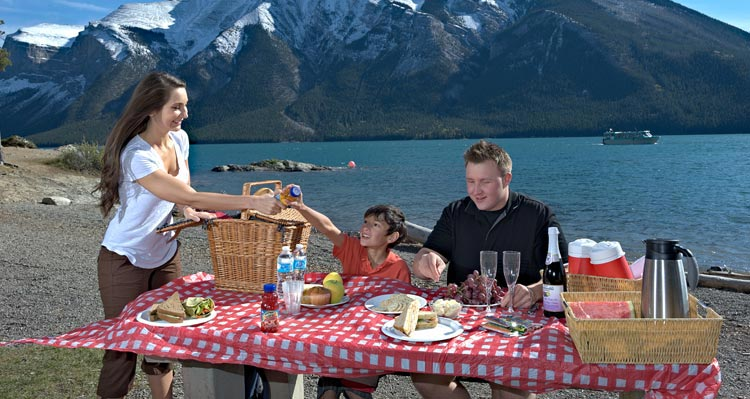 A family sits at a picnic table next to a large lake with a spread of food and drinks.
