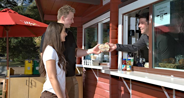 Two people getting snacks at an outdoor wooden snack shop.