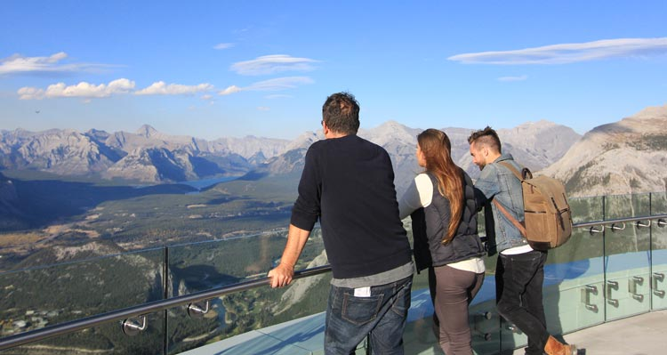 Three people look out at a wide valley and mountains from the top of the Banff Gondola.