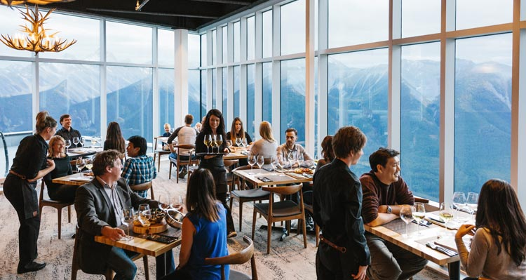 Busy restaurant tables at Sky Bistro, with floor-to-ceiling windows revealing wide mountain views.