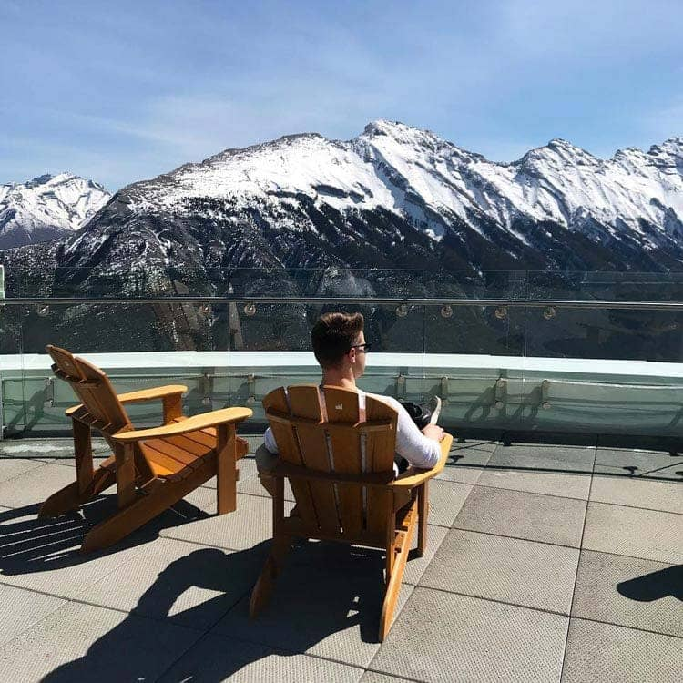A person sits in a wooden Adirondack chair looking out towards snow-covered mountains.