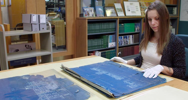 A museum researcher looks at historic blueprints in the Whyte Museum archives.